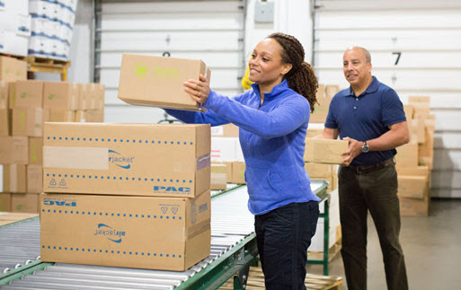 Two workers with boxes in a warehouse